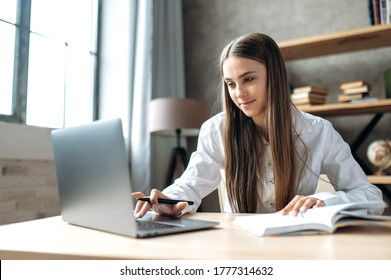 A beautiful caucasian female student is studying in college remotely. She is sitting at a table at home with a laptop and a notepad and concentrated is watching a video conference lesson