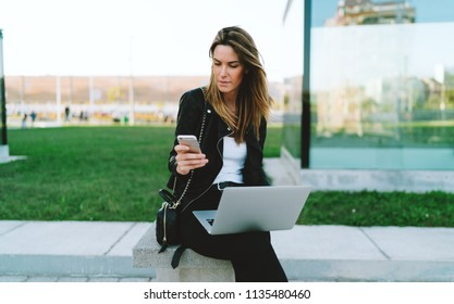 Beautiful caucasian female waiting for sms on her mobile phone to confirm transaction for online payment for the flight tickets. Student girl reading emails on a smartphone while sitting with a laptop