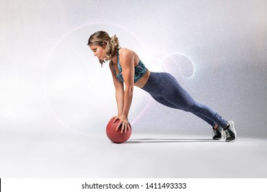Beautiful Caucasian fitness model wearing long fitness outfit and flower patterned sports bra doing a balance pushup on a ball