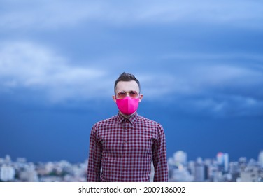 Beautiful caucasian gay in pink protective medical face mask looking straight in camera. Male person portrait with rainy weather background and urban skyline. LGBTQ theme concept. High quality iimage