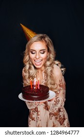 Beautiful caucasian girl blowing candles on her cake. Celebration and party