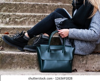 beautiful caucasian girl with a green leather bag