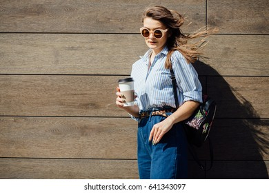 beautiful caucasian girl holding disposable cup over wooden wall on the street the wind in your hair sun street fashion clothing. close up