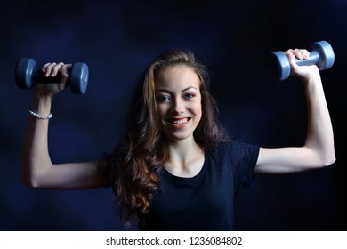 Beautiful caucasian girl holding in hands the dumbbells on dark background.