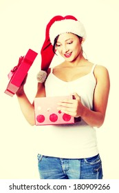 Beautiful caucasian girl holding open gift and looking what is in it.