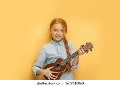 beautiful caucasian girl learns to play ukulele isolated over yellow background. attractive child with natural red hair hold small guitar, ukulele in hands and look at camera, smile, enjoy music