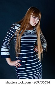 Beautiful caucasian girl with long blond hair wearing striped dress