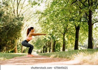 Beautiful caucasian girl practicing sport doing squat working out in the park
