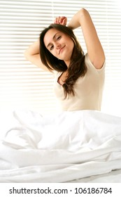A beautiful caucasian girl stretching on a bed on a light background