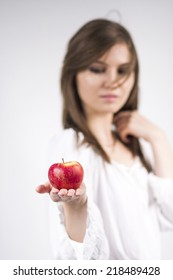 Beautiful caucasian girl wearing a white blouse, holding a red apple with light grey background