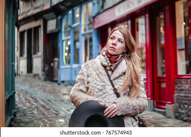 beautiful Caucasian girl wearing a white coat and and a hat in Honfleur