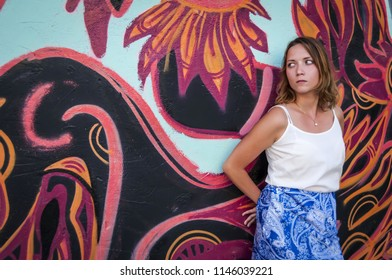 A beautiful Caucasian girl in a white shirt and a long blue skirt leaning on a colorful mural graffiti in Tel Aviv, Israel. She is looking aside. Tel Aviv party, Tel Aviv urban graffiti art concept