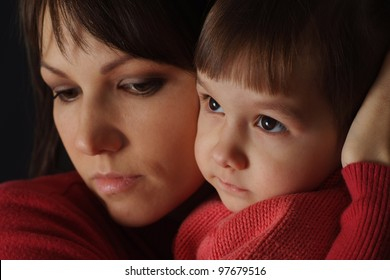 A beautiful caucasian good mother holding her daughter in her arms on a black background