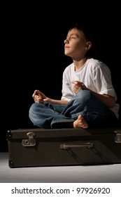 Beautiful Caucasian happy boy sitting on a suitcase on a black background