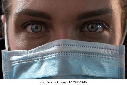 Beautiful caucasian infected girl on black background in medical mask with inscription 2019-nCov. Coronavirus covid-19 concept. Pandemic global spread