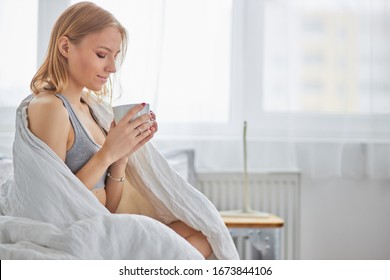 beautiful caucasian lady sit drinking hot tea or coffee on bed at home, in morning. blond female in underwear just woke up
