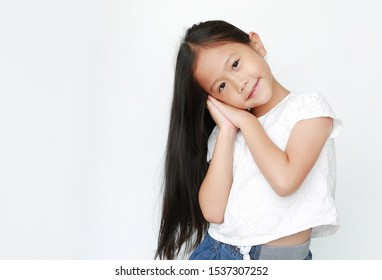 Beautiful caucasian little child girl sleep gesture posing with hands together smiling with looking at camera isolated over white background.
