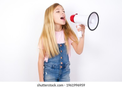 beautiful caucasian little girl wearing jeans overall over white background Through Megaphone with Available Copy Space