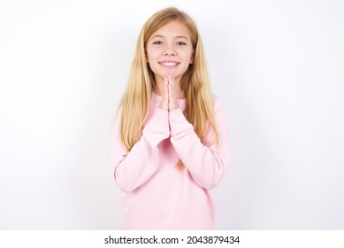 beautiful caucasian little girl wearing pink sweater over white background keeps palms together, has pleased expression. Glad attractive male makes request, pleads for mercy. Hopeful young adult.
