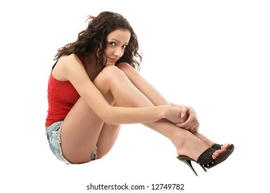 beautiful caucasian long-legged model sitting in jeans shorts and high-heeled shoes