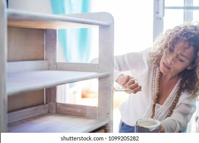 beautiful caucasian middle age independent woman paint and renew an old furniture at home with white shabby chic color. Do it yourself lifestyle for lonely and indipendent female. window light