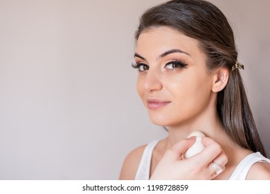Beautiful caucasian model close-up looking straight and smiling during make-up session. The make-up artist is applying the foundation on the neck. The model has white, clean complexion.