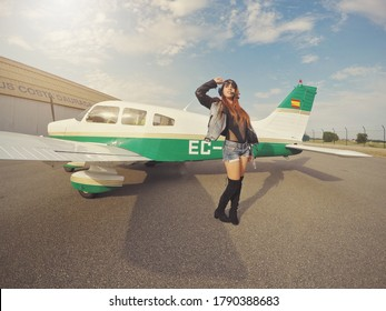 Beautiful caucasian model posing in front of a small airplane