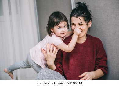 Beautiful Caucasian mother and her child playing together at home. Girl and mom in casual sitting on th carpet. Happy mum and kid having fun, smiling and hugging. Family holiday and togetherness.