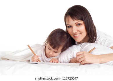 A beautiful Caucasian mother with her daughter lying on the bed with a pencil