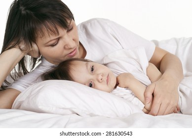 A beautiful Caucasian mummy with her daughter lying in bed
