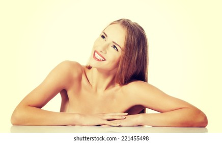 Beautiful caucasian naked woman lying on a table. Isolated on white.