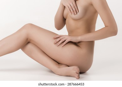 Beautiful caucasian naked woman sitting with fresh clean skin on the white background