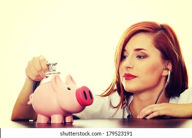 Beautiful, Caucasian nurse listening to a piggy bank with a stethoscope.