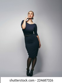 Beautiful caucasian plus size secretary in dark blue dress. Full length portrait of attractive young female posing over grey background.
