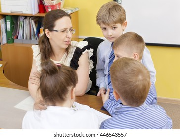 Beautiful caucasian primary school teacher and the students at the table. Three boys and a girl. Horizontal color image.