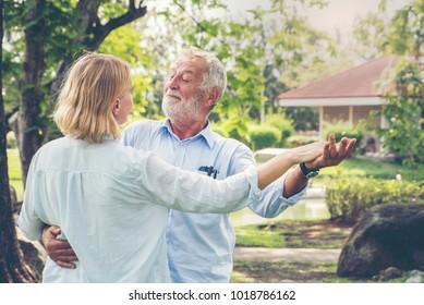 Beautiful caucasian senior couple dancing in the park