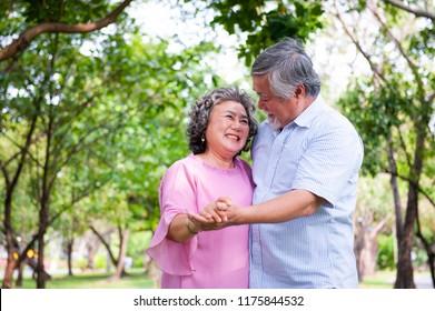 Beautiful caucasian senior couple in the park dancing. Outdoors.