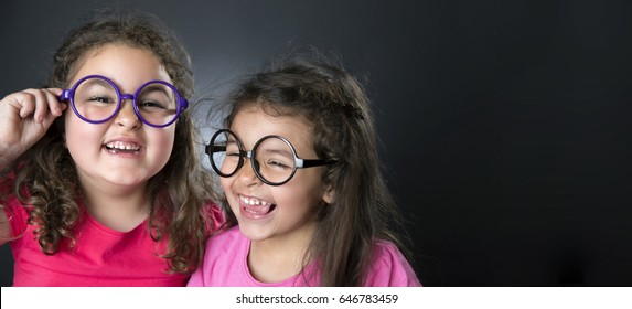beautiful caucasian sisters with glasses very happy in black background