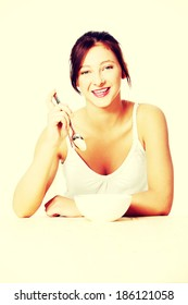 Beautiful caucasian smiling girl sitting behind the table with bowl and spoon.
