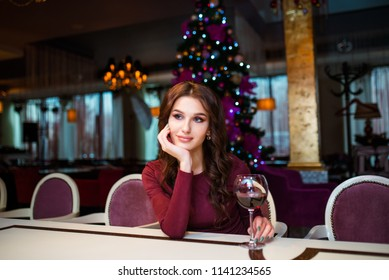 Beautiful caucasian smiling young happy woman in red dress, Christmas hat and garland of tinsel standing with glass of champagne on white background. Santa girl isolated. New Year holiday concept.