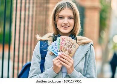 Beautiful caucasian student teenager using headphones holding canadian dollars at the city.