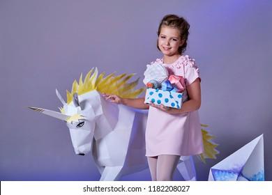 Beautiful caucasian teen girl in elegant pink dress holding box of origami. Fashion kid eve Christmas,new year,holiday. Child portrait make-up. Pastel background,studio. White unicorn origami near.
