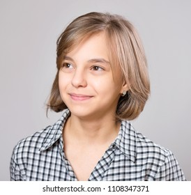 Beautiful caucasian teen girl on gray background. Schoolgirl smiling and looking away. Happy child - emotional portrait close-up.