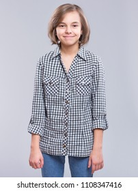 Beautiful caucasian teen girl, on gray background. Schoolgirl smiling and looking at camera. Happy child - half-length emotional portrait.