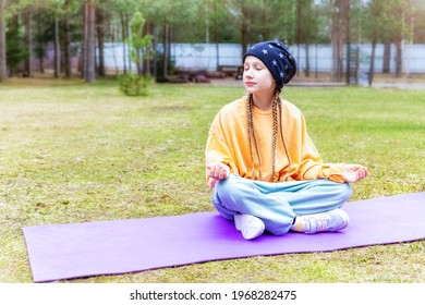 Beautiful caucasian teenage girl sitting on a sports mat outdoors, meditating with her eyes closed. Healthy lifestyle, sports, yoga. Mental health, relaxation. Comfortable sportswear.