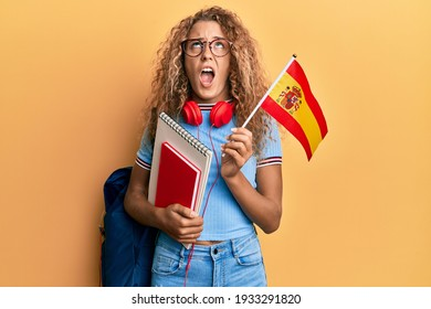 Beautiful caucasian teenager girl exchange student holding spanish flag angry and mad screaming frustrated and furious, shouting with anger looking up.