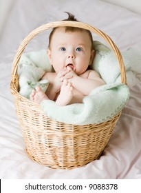 A beautiful caucasian white baby girl portrait with cute facial expression lying in a basket