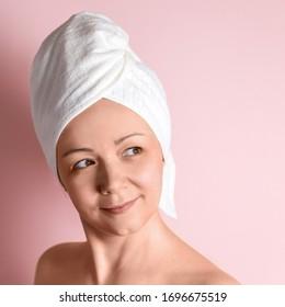 Une belle femme caucasienne après une douche. Elle regarde au loin. Procédures pour le rajeunissement du visage, l'autosoin, la peau saine. Elle est heureuse.
