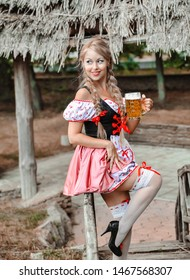 Beautiful caucasian woman with beer in dress. Octoberfest festival.
