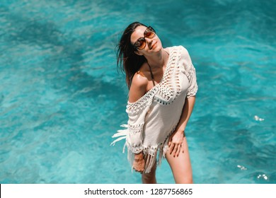 Beautiful Caucasian woman with brown hair and sunglasses posing on the beach. In background ocean.